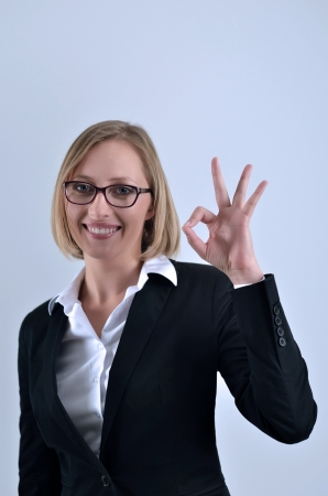 Young beautiful businesswoman hand gesturing okay sign photo
