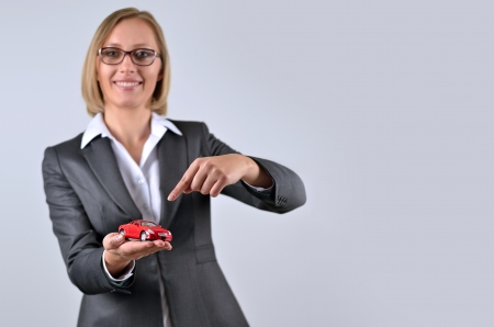Young and beautiful business woman holding a toy car on her hand photo