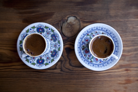 Two cups of Turkish coffee on wooden table photo