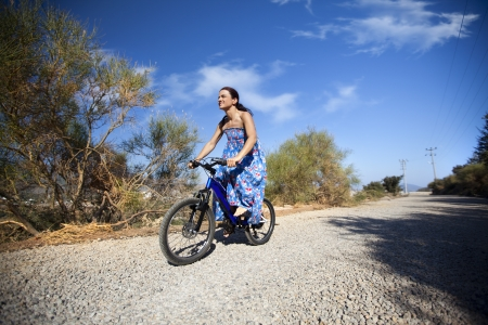 Happy young woman riding on a bicycle on a countryside road photo
