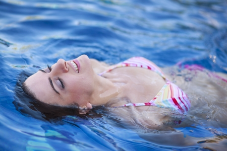 Young woman enjoying water and sun in outdoor swimming pool during summer vacation photo