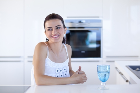 Portrait of beautiful relaxed young woman thinking in the her kitchen photo