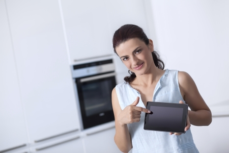Beautiful woman holding a digital tablet and pointing to screen in the her kitchen photo