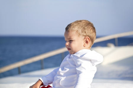 lovely young boy is sitting on the boat photo