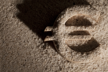Wooden economy and currency unit in sand with shodow photo