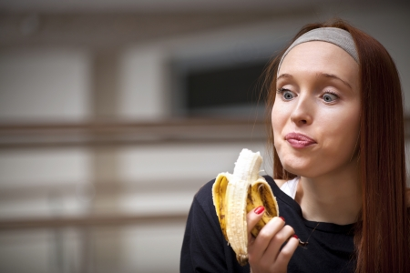 Woman eating banana at the gym for energy photo