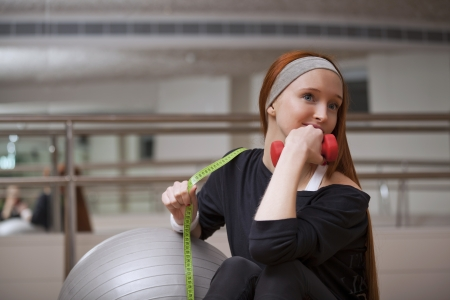 Woman is sitting with fitness ball, weights and measure photo