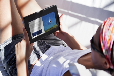 carefree woman uses touch pad tablet technology at the poolside photo