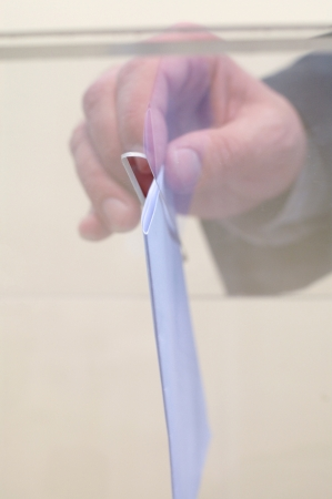 Image of a ballot box and hand putting a blank ballot inside,elections, voting concept photo