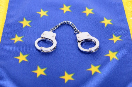 Flag of European Union and handcuffs,  European Union law concept