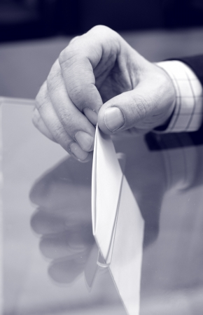 campaigning: Image of a ballot box and hand putting a blank ballot inside,elections, voting concept