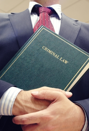 Lawyer holding criminal law book , law concept , justice concept