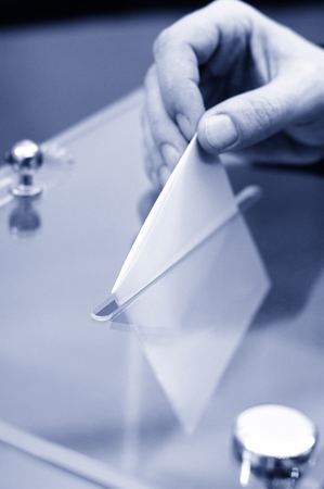 mp: Image of a ballot box and hand putting a blank ballot inside,elections, voting concept, blue toned