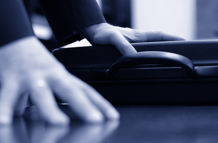blue  toned: Business meeting detail, businessman hand on the briefcase closeup blue toned Stock Photo