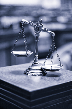 Symbol of law and justice in the empty courtroom, law and justice concept, blue toned.