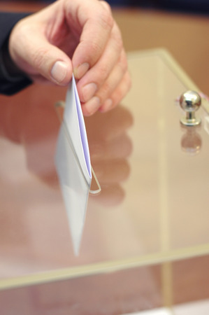 Image of a ballot box and hand putting a blank ballot inside,elections, voting concept.