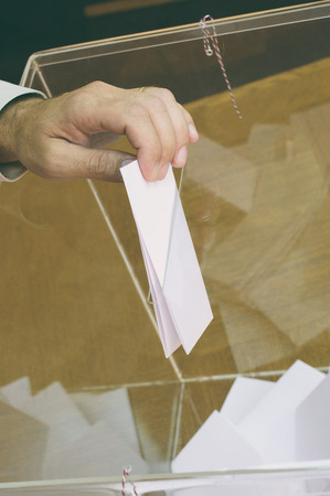 mp: Image of a ballot box and hand putting a blank ballot inside,elections, voting concept.