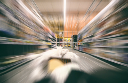 Shopping cart with groceries moving through supermarket, shopping concept. Stock Photo