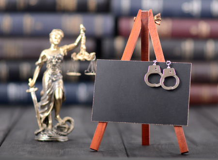 Blackboard, handcuffs, Lady Justice on the wooden background