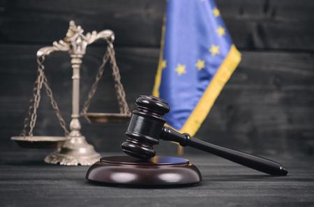 Legge e giustizia, concetto di legalità, bilancia della giustizia, giudice Gavel e bandiera dell'Unione europea su un fondo di legno nero.