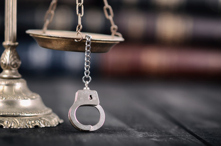 Law and Justice, Legality concept, Scales of Justice and handcuffs on a black wooden background.
