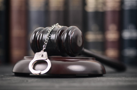 Law and Justice, Legality concept, Judge Gavel and Handcuffs on a black wooden background. Stock Photo