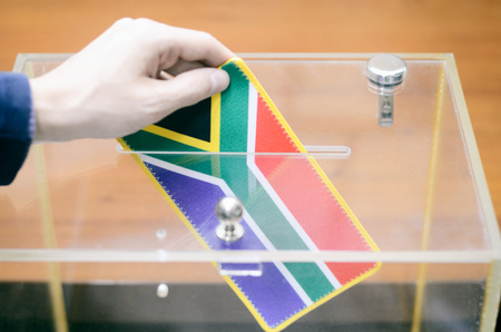 Man inserting Flag of South Africa into ballot box, voting and elections in South Africa. Фото со стока