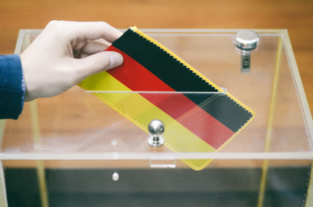 Man inserting Flag of Germany into ballot box, voting and elections in Germany.