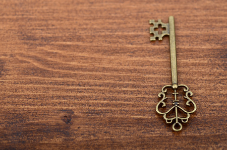 Old vintage key on a wooden background. Stock Photo