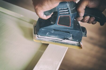 Sanding and preparing old doors with cracked paint for a new lick of paint, Smooth sanding or paint removal concept. Banque d'images - 136119603