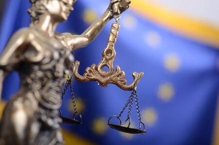 Legge e giustizia, concetto di legalità, bilancia della giustizia, giustizia, signora giustizia davanti alla bandiera dell'Unione europea sullo sfondo.