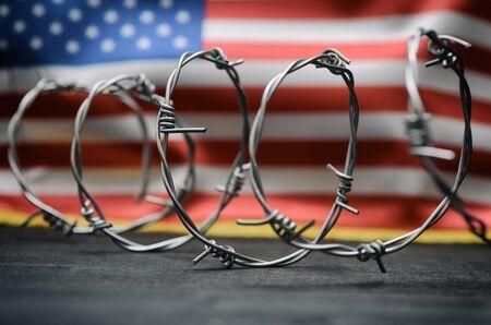 Alambre de púas y bandera de Estados Unidos de América, concepto de inmigración.