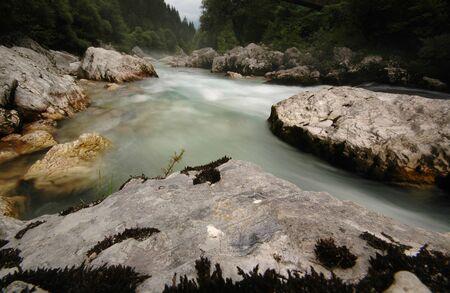 Emerald green river Soca in Slovenia, foggy water stream of Soca river