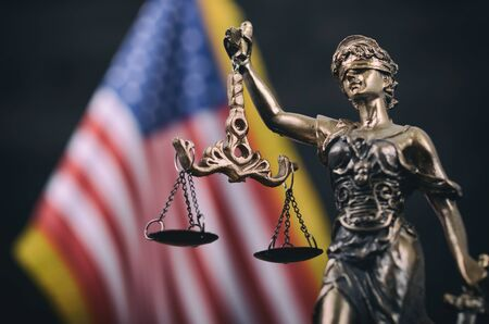 Ley y justicia, concepto de legalidad, balanza de la justicia, Justitia, Lady Justice frente a la bandera estadounidense de fondo.