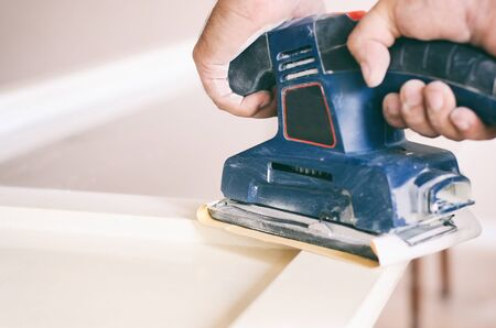 Sanding and preparing old doors with cracked paint for a new lick of paint, Smooth sanding or paint removal concept.