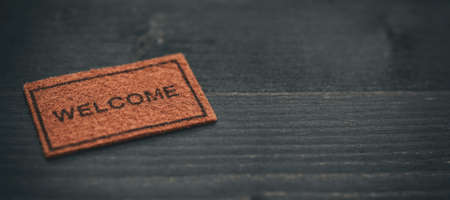 Old Welcome door mat on black wooden background, welcome concept, home concept