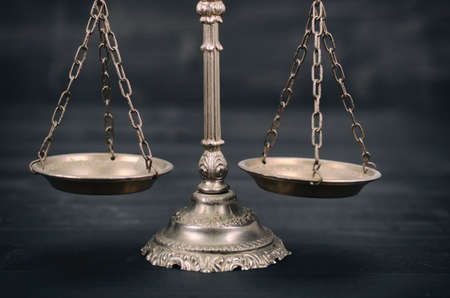 Law and Justice, Legality concept, Scales of Justice on a black wooden background. Standard-Bild