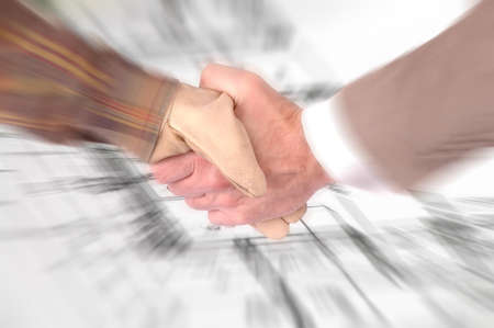 Worker and a businessman shaking hands over house renovation plans