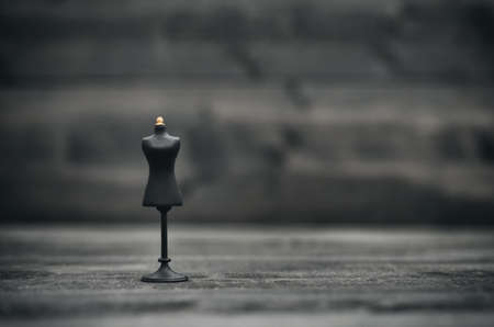Fashion design concept, vintage mannequin stand on black wooden background Standard-Bild