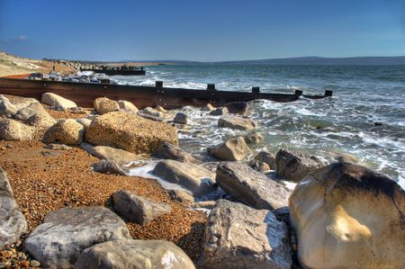 hdr background: HDR Image of Groynes protecting  the coast with rugged  rocks in foreground
