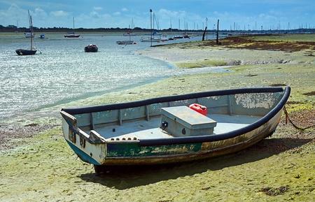 estuary: Boat on mud in estuary at low tide at Emsworth UK