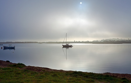 murky: Dark murky and misty weather with boats in estuary at Calshot, Hampshire UK Stock Photo