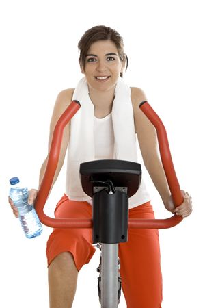 Young woman training on exercise bike at the gym whit a bottle of water on the left hand Stock Photo