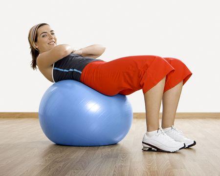 n�cleo: Mujer joven hermosa que hace ejercicios con una bola de la base