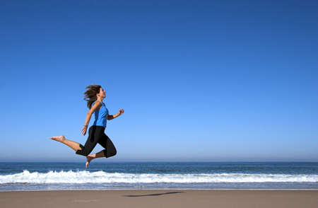 Young atractive woman running and jumping on the beach Stock Photo