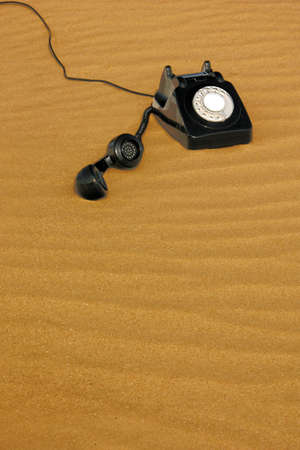 the outdated: Old dial phone in the sand. Stock Photo