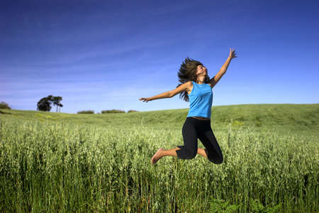 Young active woman jumping on a green field