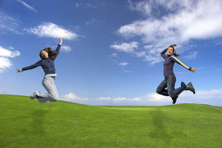 Girls jumping on the green field Stock Photo
