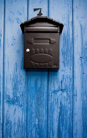locked door: Mailbox in a blue door