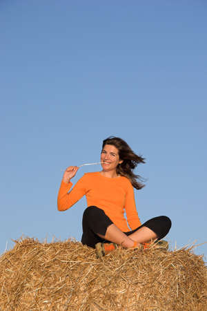 Beautiful woman seated in a field photo